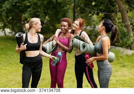 Multinational Women With Yoga Mats Talking And Laughing After Outdoor Yoga Class
