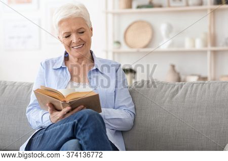 Favorite Pastime. Smiling Elderly Lady Reading Book On Comfortable Couch At Home, Enjoying Retiremen