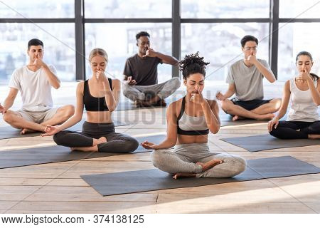 Young Men And Women In Yoga Studio Practicing Alternate Nostril Breathing Exercises Together, Sittin