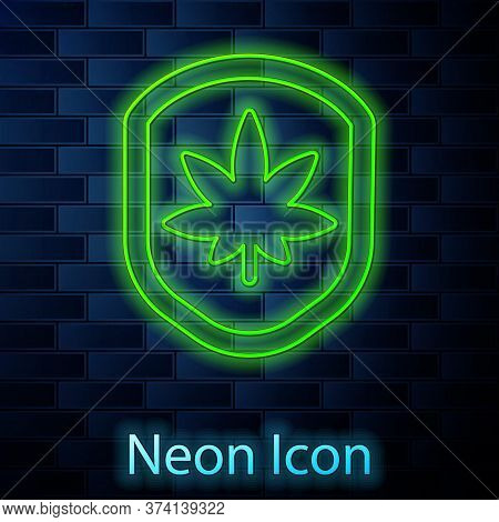 Glowing Neon Line Shield And Marijuana Or Cannabis Leaf Icon Isolated On Brick Wall Background. Mari