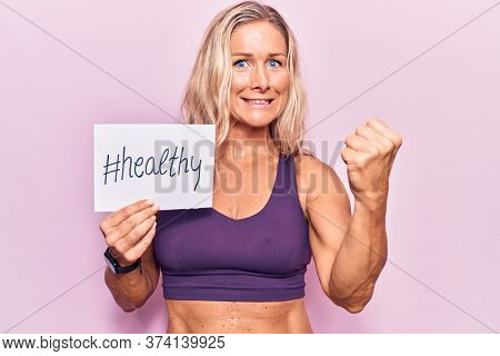 Middle age caucasian blonde woman wearing sportswear holding healthy banner annoyed and frustrated shouting with anger, yelling crazy with anger and hand raised