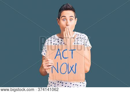 Young woman with short hair holding act now banner covering mouth with hand, shocked and afraid for mistake. surprised expression