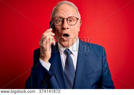Grey haired senior business man having a conversation talking on smartphone over red background scared in shock with a surprise face, afraid and excited with fear expression