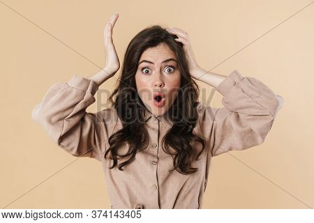 Image of shocked brunette woman posing and grabbing her head isolated over beige background