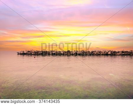 Colorful Dramatic Sunset With Cloudy Sky Over The Tranquil Sea. Rocky Pier With Birds. Nature Backgr