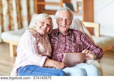 Happy retired couple retired with tablet computer at home