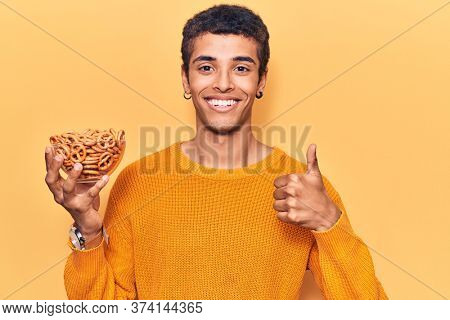 Young african amercian man holding pretzels smiling happy and positive, thumb up doing excellent and approval sign