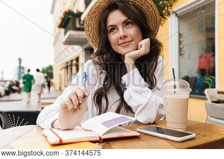 Portrait of young pleased woman writing down notes while drinking milkshake in cozy cafe outdoors