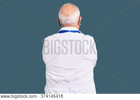 Senior handsome grey-haired man wearing doctor coat and stethoscope hugging oneself happy and positive from backwards. self love and self care