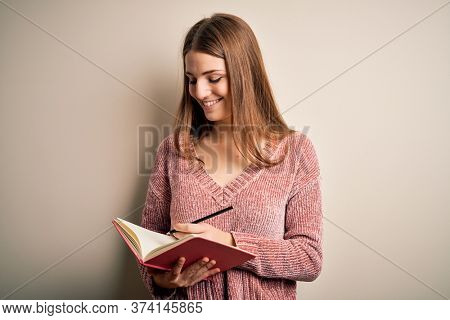 Young beautiful redhead student woman reading book over isolatated white background with a happy face standing and smiling with a confident smile showing teeth