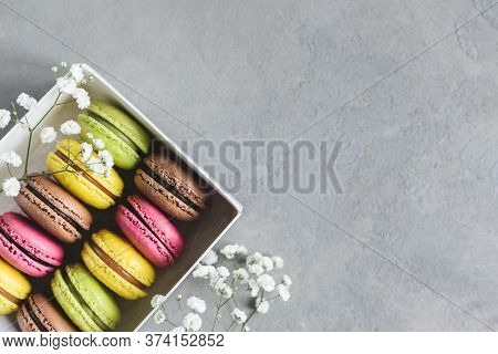 Set Of Tasty Multi-colored French Macaroons On A Grey Background. Pink, Green And Brown Macaroons. P