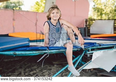 Gymnast Sitting On Trampoline In Fitness Center. Tired Child Sits On Trampoline After Jumping While