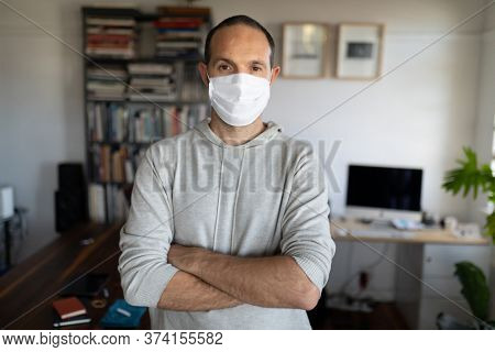 Portrait of Caucasian man spending time at home self isolating and social distancing in quarantine lockdown during coronavirus covid 19 epidemic, wearing a face mask and looking at camera