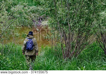 Active Man In Mosquito Suit With Backpack In Hiking Near Taiga River In A Siberian Forest, Russia. S