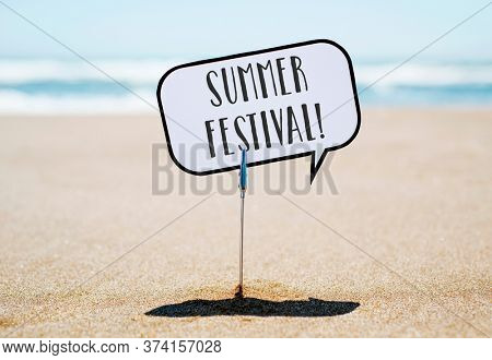 closeup of a speech balloon, with the text summer festival written in it, stuck on the sand of a quiet beach, with the sea in the background