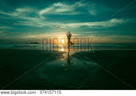 Silhouette of a woman practicing yoga on a sea beach in a surreal sunset.