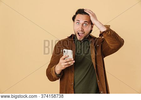 Image of astonished man expressing surprise while using mobile phone isolated over beige background