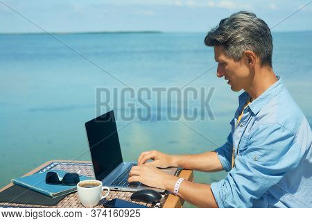 Business Man Working On The Beach At Morning By The Sea, Using Laptop. Freedom, Remote Work, Freelan