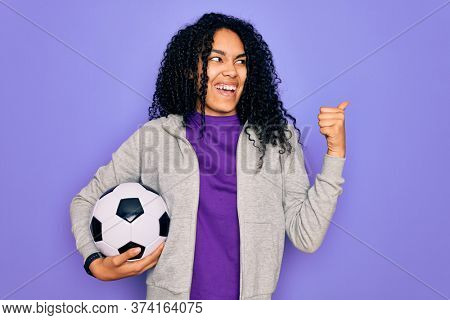 African american curly player woman playing soccer holding football bal over purple background pointing and showing with thumb up to the side with happy face smiling