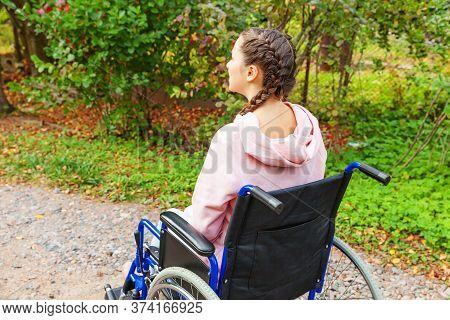 Young Happy Handicap Woman In Wheelchair On Road In Hospital Park Waiting For Patient Services. Para