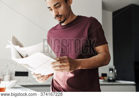 Photo of concentrated african american man with beard reading newspaper in kitchen at home