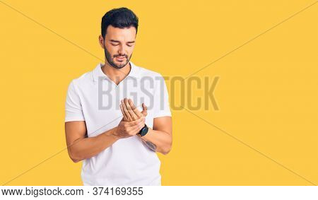 Young handsome hispanic man wearing casual clothes suffering pain on hands and fingers, arthritis inflammation