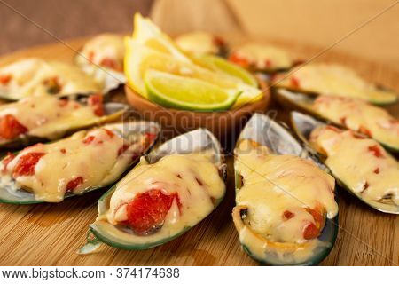 Seafood. Mussel Clams. Baked Greenshell Mussels With Tomato And Cheese, Cilantro And Lemon On Wooden