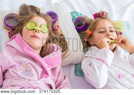 Two Daughters With Cucumbers On Eyes With Curlers In Hair Lying On The Bed In The Bedroom. Stay Home