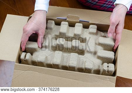 Woman's Hands While Unpacking A New Box With An Product