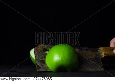Green Apple On A Black Background. Kitchen Hatchet Chopping An Apple In Half. Hatchet Old With Rust