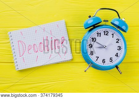 Flat Lay Deadline Concept. Blue Alarm Clock With Notepad With Deadline Word On Yellow Wood.