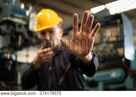 Selective Focus Of Industrial Worker In Factory Site Gesture Keep Out While Communicating With A Wal