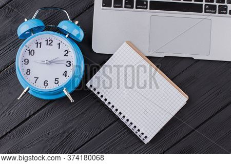 Notepad With Blank Pages For Copy Space. Flat Lay Alarm Clock With Laptop Pc And Notepad On Dark Woo