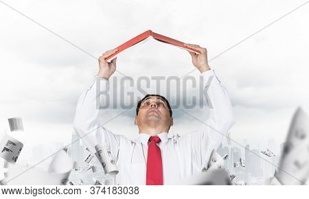 Senior Businessman Holding Open Diary Overhead. Man In Shirt And Tie Standing On Cityscape Backgroun