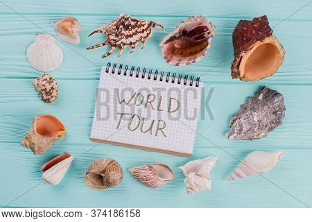Along The Perimeter Are Different Sea Shells On Turquoise Background. World Tour On The Notebook.