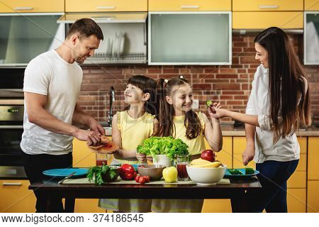 The Concept Of Healthy Eating. A Young Happy Family With Two Daughters Stand At The Table And Prepar
