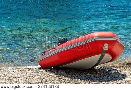Red Rescue Inflatable Boat, Closeup. Empty Marine Rescue Boat. Inflatable Boat On The Beach It Is Re