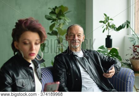 Family Portrait Of Adult Daughter And Senior Father In Loft Room With Houseplants. Man And Girl Are