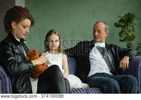 Family Portrait Of Adult Daughter, Little Granddaughter And Senior Grandfather In Loft Room With Hou