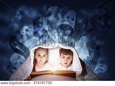 Engrossed Little Kids Reading Book In Bed. Brother And Sister Together Hiding Under Blanket. Fearful