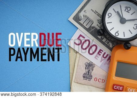 Overdue Payment Text With Alarm Clock, Banknotes Currencies And Calculator On Blue Background. Coron