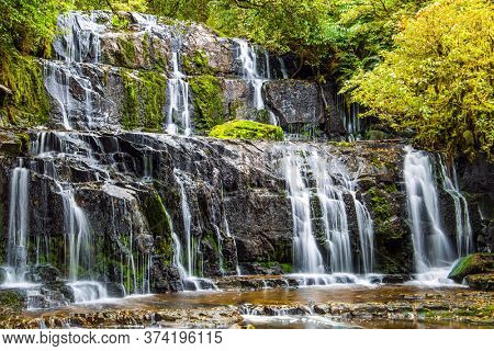 South Island, New Zealand. Picturesque multi-tiered cascading waterfalls among the green forest. Purakaunui Falls. The concept of active, environmental and photo tourism