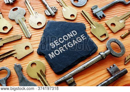 The Second Mortgage Concept. House Figurine And Many Keys.