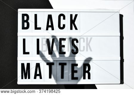 Black Lives Matter Text With Deep Shadows Of Hand On A Black And White Background. Protest Against T