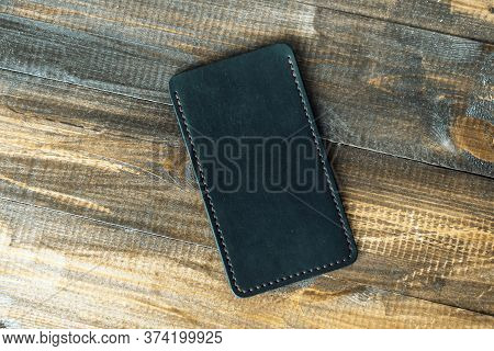 Leather Luxury Phone Case On A Wooden Background. Beautiful Genuine Leather Phone Case.
