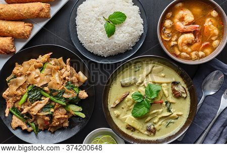 table of thai restaurant foods with green, pad see ew noodles and tom yum goong soup