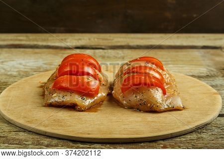 Chicken Breast In Marinade Stuffed With Tomatoes On A Round Wooden Board. Copy Space.