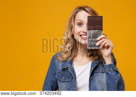 Smiling Young Woman In Denim Clothes Isolated On Yellow Orange Background. Proper Nutrition Or Sweet