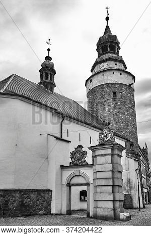 A Medieval, Stone Church With A Bell Tower And A Fragment Of The City Gate In Jelenia Gora In Poland