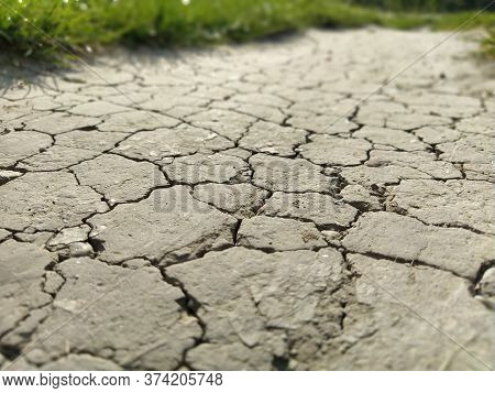 Cracked Sidewalk In Urban Area. Cracked Dirt Road With Cracks In The Clay Structure Of The Soil. On